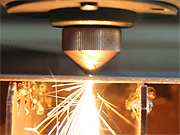 close up of laser cutting metal with sparks